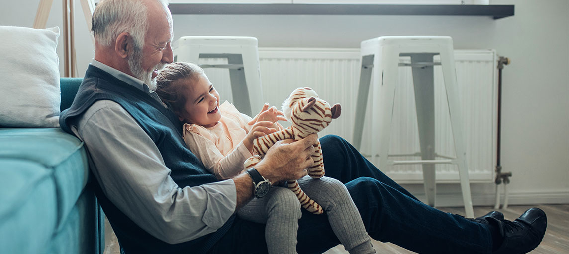 Elderly man holding his granddaughter