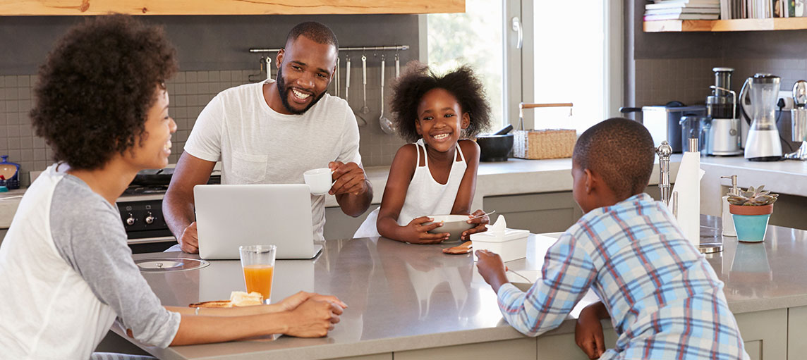 Family Sitting In Kitchen Enjoying Morning Breakfast Together